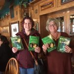 Two ladies holds up Joe's books at the Kiwanis Club book signing
