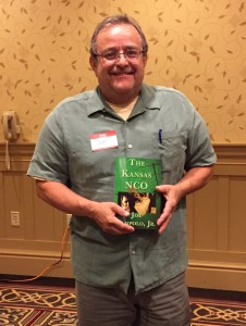 Joe holds up his book The Kansas NCO at a Red Engine Press event