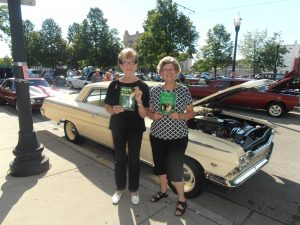 Two ladies holds up Joe's books at the Downtown Kenosh car show