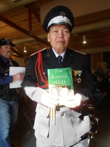 Hmong Vietnam War Veteran holds up the Kansas NCO book