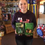 Young girl holds up Joe's books at the Highground gift shop