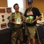 Two senior men hold up Joe's books at the TFW reunion