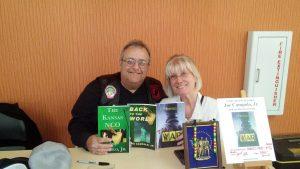 Joe and a lady holds up the Kansas NCO books