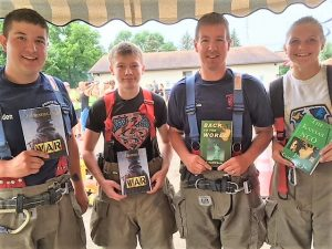 Volunteer firefighters hold up Kansas NCO Trilogy books
