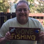 Joe holds up a Gone Fishing sign