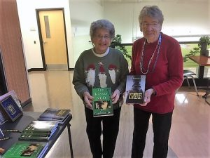 Two senior ladies holding up the Kansas NCO and Three Wars books